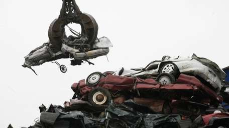 A crane lifts a flattened car from a