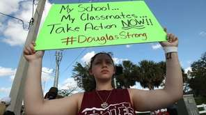 Student Angelia Lazo holds up a sign on