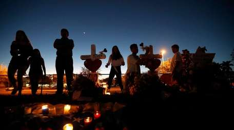 People visit a makeshift memorial outside Marjory Stoneman