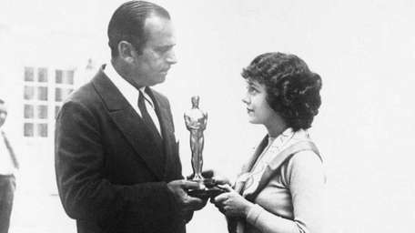 Actress Janet Gaynor accepts a merit trophy from