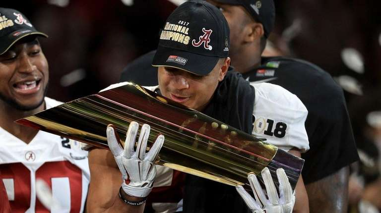 Alabama's Minkah Fitzpatrick holds the trophy after defeating