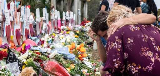 People visit a makeshift memorial in front of