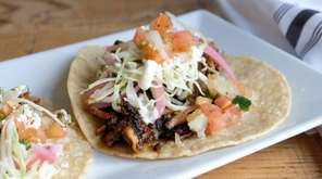 Carnitas tacos, served on housemade corn tortillas, are