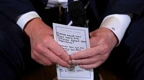 President Donald Trump holds his notes while hosting