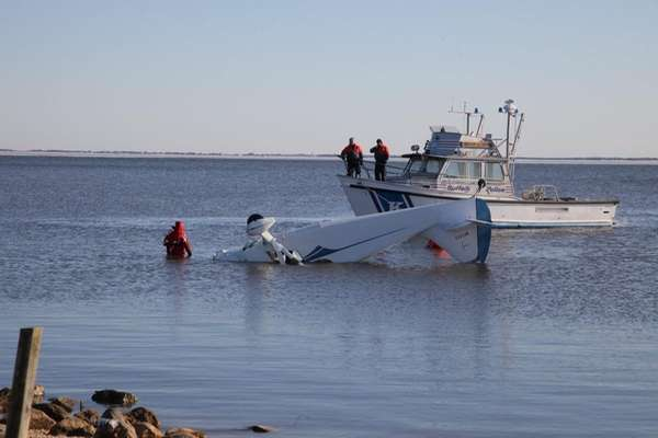 Rescue workers survey a single-engine plane that crashed