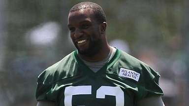 David Harris of the Jets laughs while stretching during