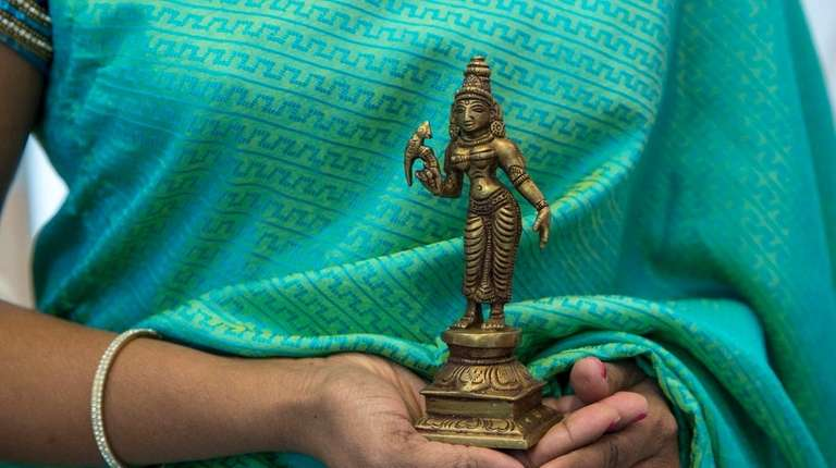 Prabha Swaminathan holds a standing Meenakshi statue on