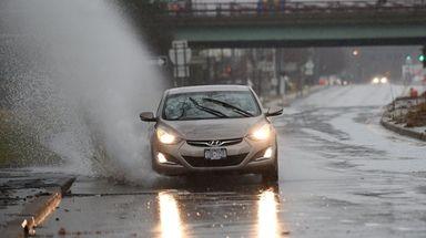 A car navigates through a large puddle on