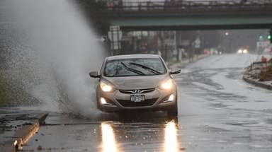 A car navigates through a large puddle on