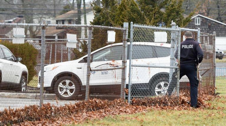 A Suffolk County police investigator near a security