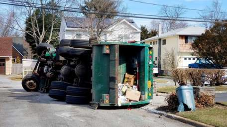 A garbage truck overturned Wednesday, Feb. 28, 2018,