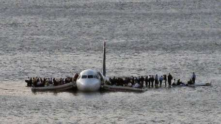 Airline passengers wait to board a ferry to