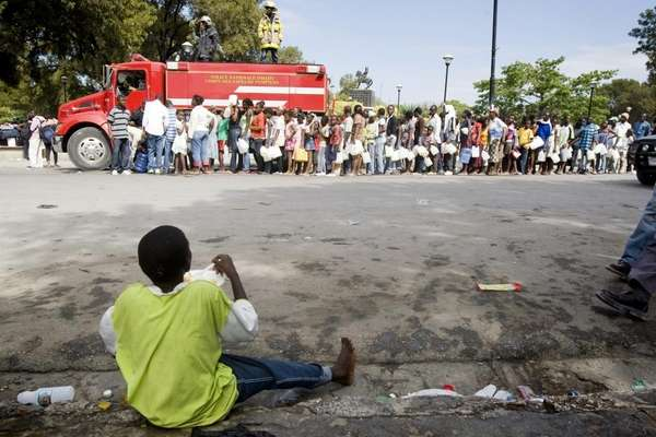 Haitians line up for water.