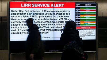 People walk past a sign advising LIRR passengers