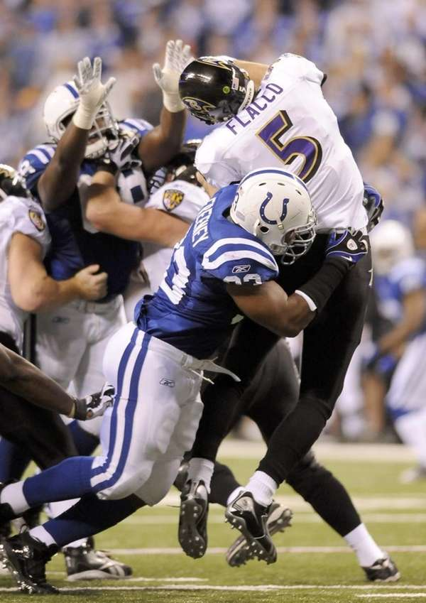 The Indianapolis Colts' Dwight Freeney (93) hits Baltimore