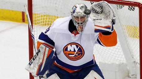 Islanders goaltender Christopher Gibson, top, gloves a shot