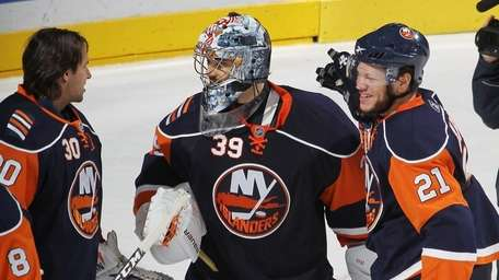 Rick DiPietro is congratulated by teammates Dwayne Roloson