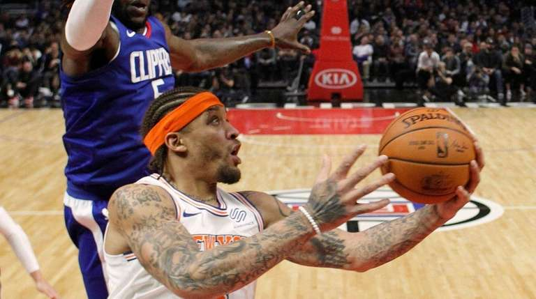 Knicks forward Michael Beasley, front, goes to the
