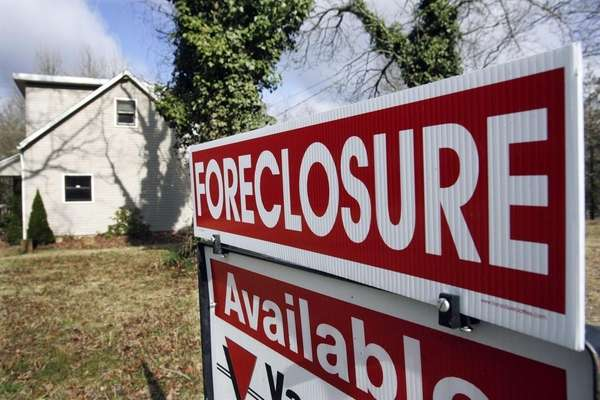 A foreclosure sign is seen on the lawn