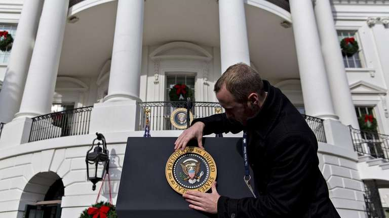 A White House staff member adjusts the presidential