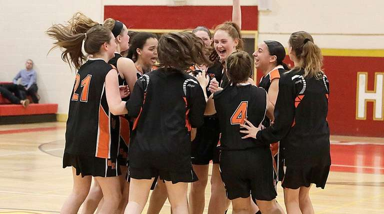 The East Rockaway girls basketball team celebrates its