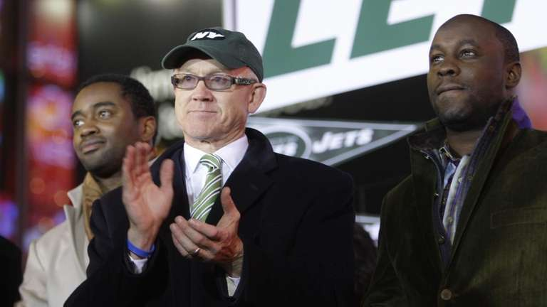 New York Jets owner Woody Johnson, center, claps