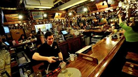 A bartender makes a drink from behind the