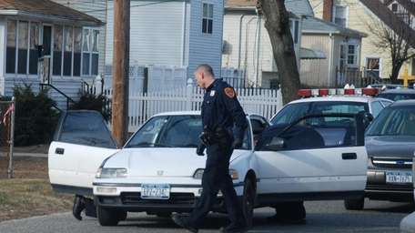 Police inspect a suspects car on Coolidge Ave