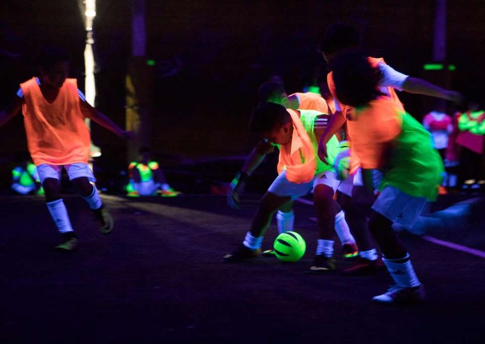 Kids play glow in the dark indoor soccer