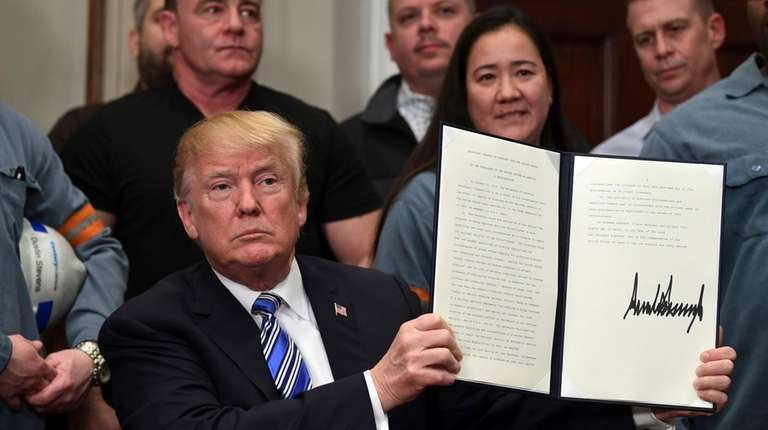 President Donald Trump holds up a proclamation on