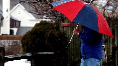 A man walks through the rain in Sayville