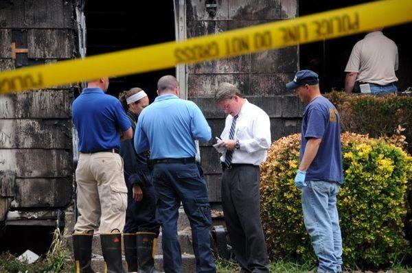 Investigators comb a Central Islip house where three