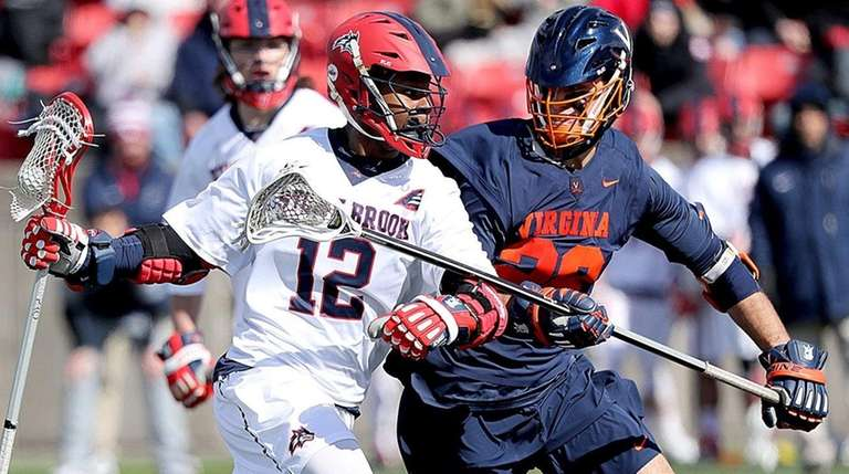 Stony Brook midfielder Wayne White drives against Virginia