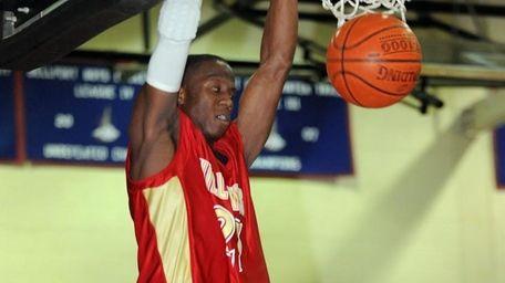Hills West's Tavon Sledge (23) dunks against Bellport.