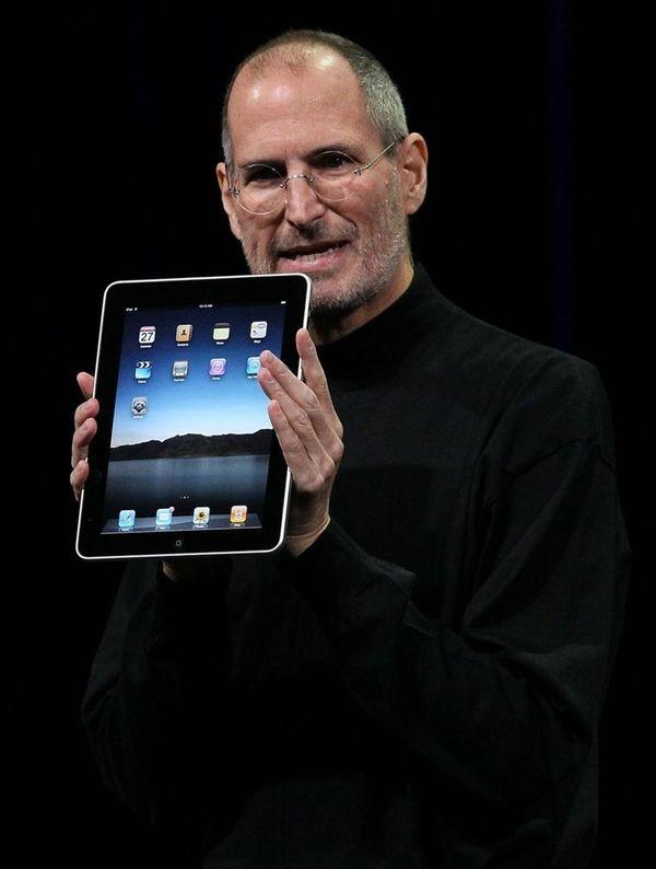Apple Inc. CEO Steve Jobs holds up the