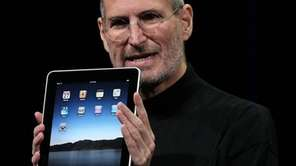 Apple Inc. CEO Steve Jobs holds up the