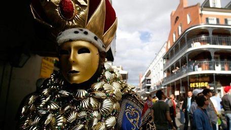 A costumed man walks down Bourbon Street in