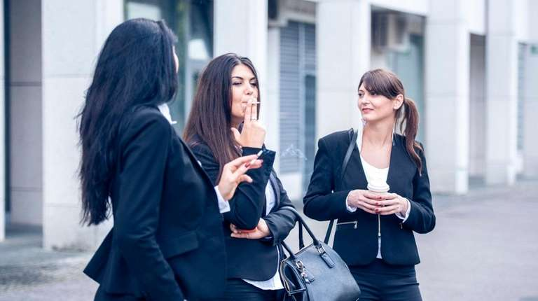 Three young business women are standing outdoors in