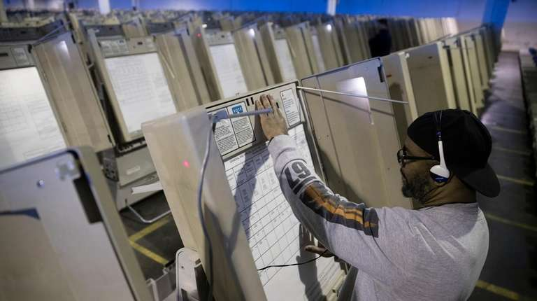 A technician works to prepare voting machines.