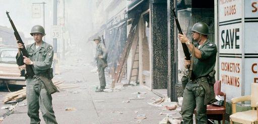 National Guardsmen patrol a riot-torn street in Detroit