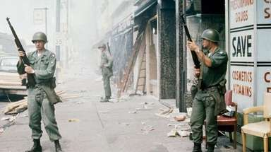 National Guardsmen patrol a riot-torn street in Detroit