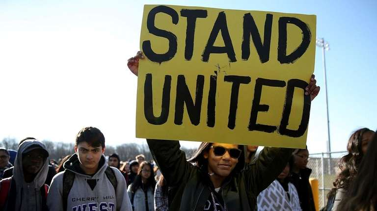 Freshman Kennedi Lawson, 14, carries a sign during