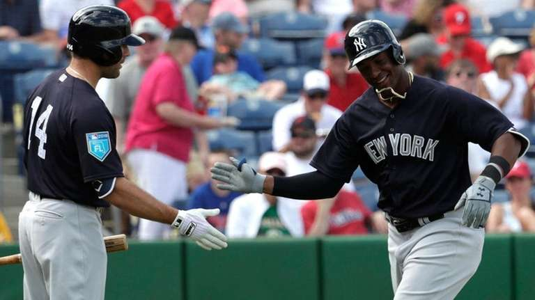 Miguel Andujar is greeted by Danny Espinosa after