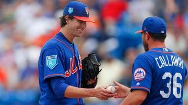 Mets starting pitcher Jacob deGrom hands the ball