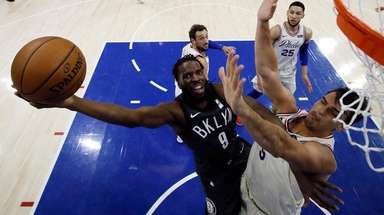 The Nets' DeMarre Carroll, left, goes up to