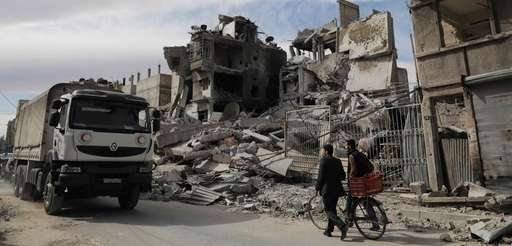 Syrians walk near a humanitarian convoy carrying food