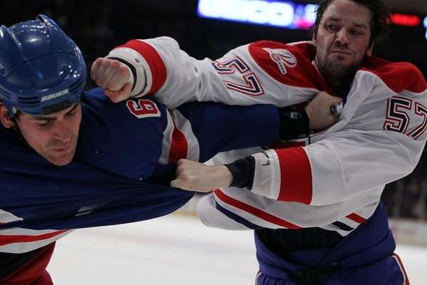 The Rangers' Wade Redden, left, fights Benoit Pouliot