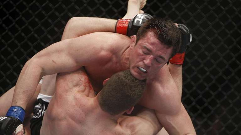 Chael Sonnen, top, grapples with Nate Marquardt during