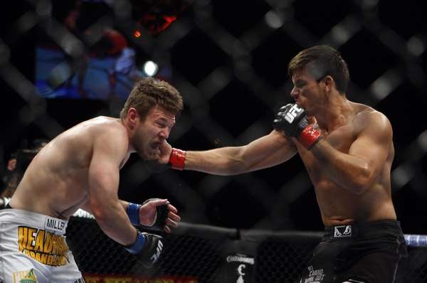 Demian Maia, right, punches Dan Miller during their