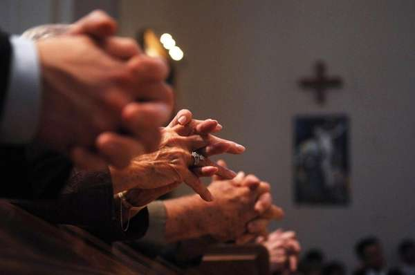 Parishioners pray during a ceremony at St. Agnes